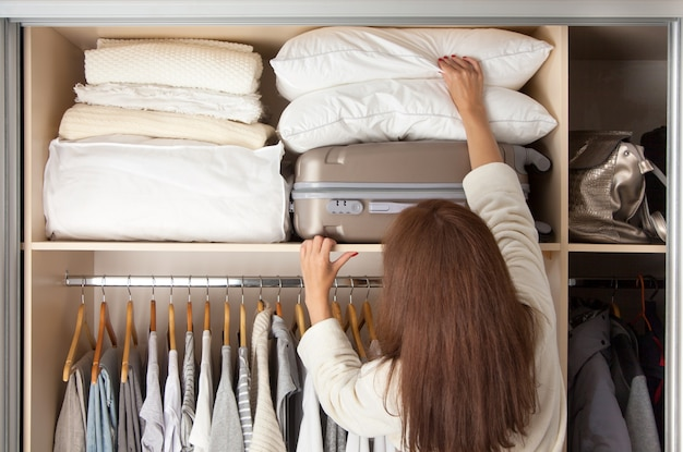 Cheerful young beautiful woman pulls out pillows from the top shelf. . copy space. storage clothes.