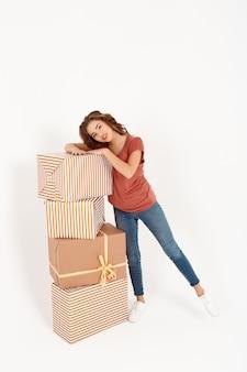큰 선물 상자 스택 옆에 서있는 쾌활한 젊은 아름다운 여자
