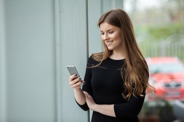 그녀의 사무실에 서있는 동안 미소로 그녀의 스마트 폰을 사용 하여 쾌활 한 젊은 아름 다운 여자.