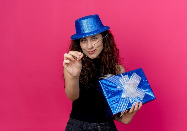 Giovane bella donna allegra con capelli ricci in un cappello di festa che tiene il contenitore di regalo di compleanno e il concetto di festa di compleanno di sparkler sopra il rosa