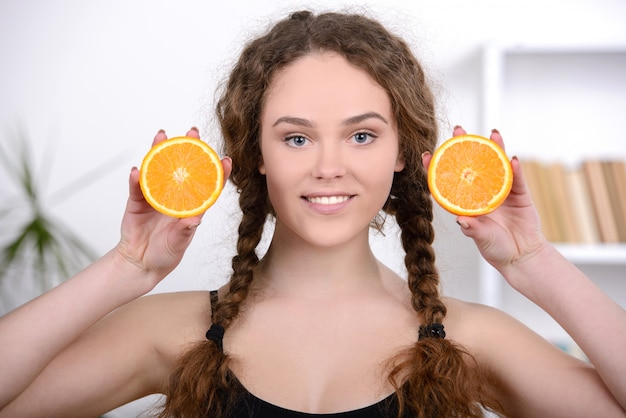 Cheerful young beautiful woman with orange.