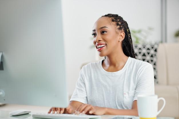 Веселая молодая черная деловая женщина сидит за офисным столом и отвечает на электронные письма от коллег и клиентов