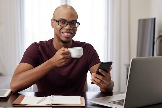 Веселый молодой черный предприниматель пьет чашку кофе и проверяет сообщения и уведомления на своем смартфоне во время короткого перерыва на работе