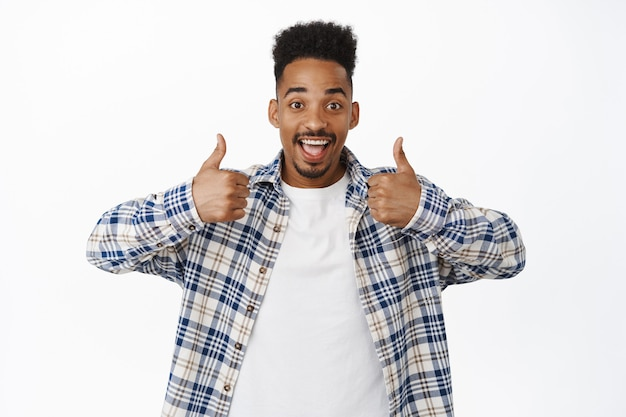 Cheerful young black guy showing thumbs up. african american man like and approve smth good, praise great deal, recommend store or company, nod in approval say yes on white