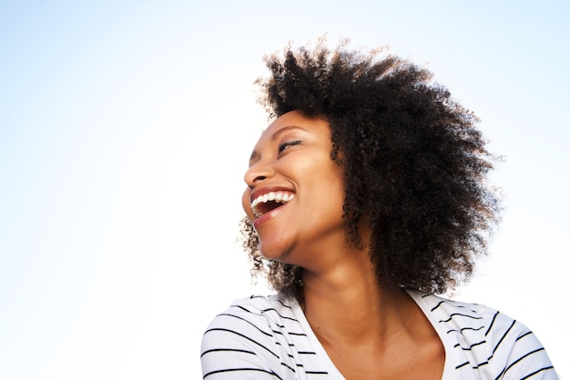 Cheerful young black woman laughing outdoors against bright sky