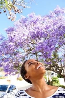 春に外を見上げている朗らかな若い黒人の女性