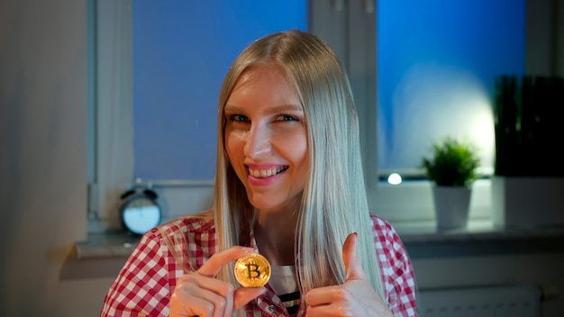 Cheerful young blond woman in casual clothes sitting at dark window at night holding bitcoin and doi...