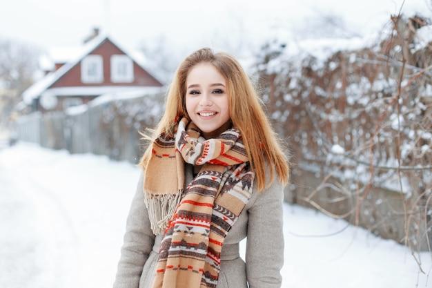 ヴィンテージのウールのスカーフと灰色の冬のコートで美しい笑顔と自然なメイクで陽気な若いブロンドの女性は、フェンスの近くの雪道に立っています。村で休暇中の幸せな女の子