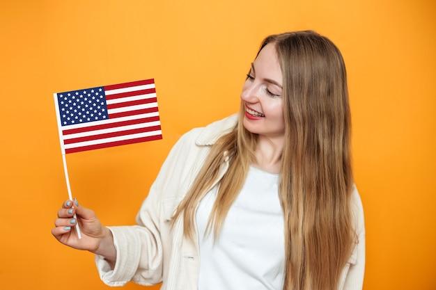 Веселая молодая белокурая студентка держит маленький американский флаг и улыбается на оранжевом фоне, девушка держит флаг сша, 4 июля в день независимости, копировальное пространство