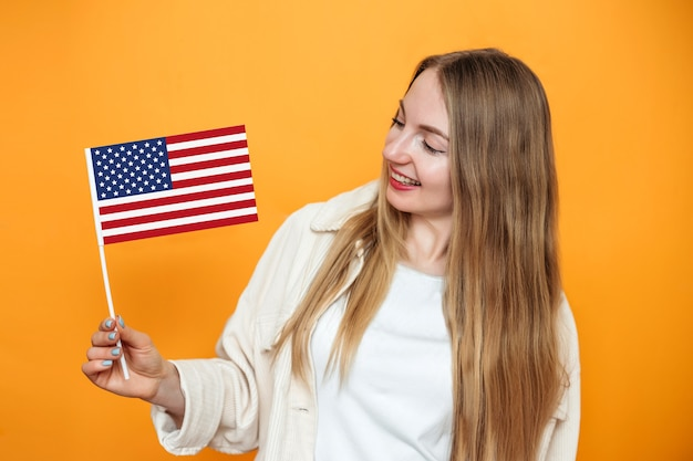 Cheerful young blonde female student holds a small american flag and smiles isolated over orange background, girl holding usa flag, 4th of july independence day, copy space