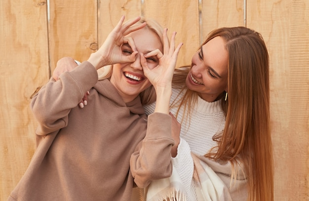 Cheerful young blonde female in trendy warm hoodie looking through fingers, while having fun with brunette girlfriend in white knitted sweater against wooden fence
