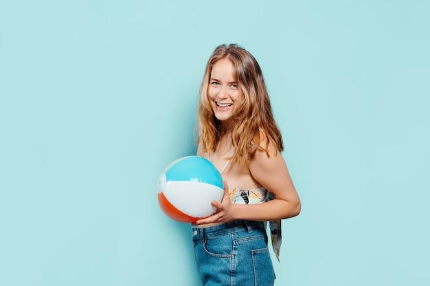 Веселая молодая блондинка смотрит в камеру с надувным мячом в летнем топе на синем фоне