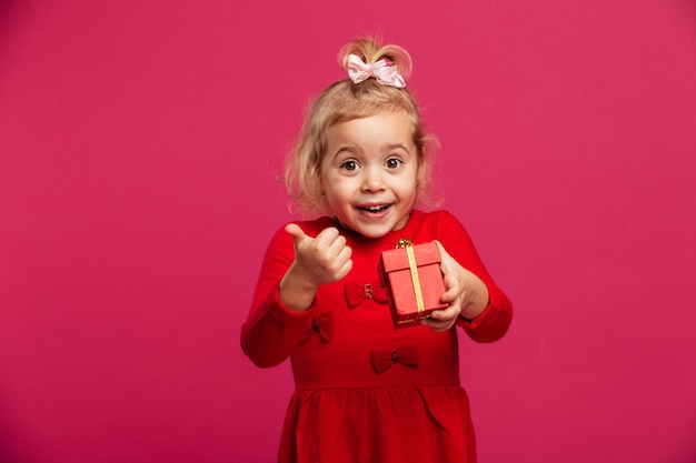 Cheerful young blonde girl in red dress holding gift box