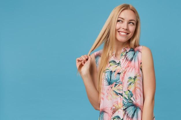 Веселая молодая блондинка с непринужденной прической, тянет за волосы и кусает нижнюю губу. позирует в романтическом платье, счастливо глядя в сторону с широкой улыбкой.
