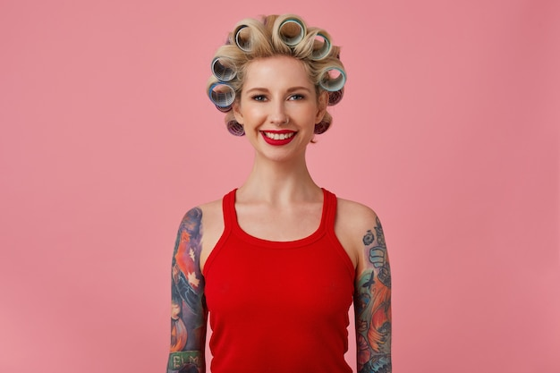 Cheerful young blonde tattooed female with evening makeup making hairdo while posing over pink background with hands down, looking at camera with charming smile