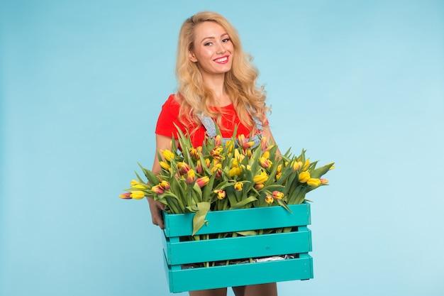 Веселая молодая блондинка флорист женщина с коробкой тюльпанов на синем.
