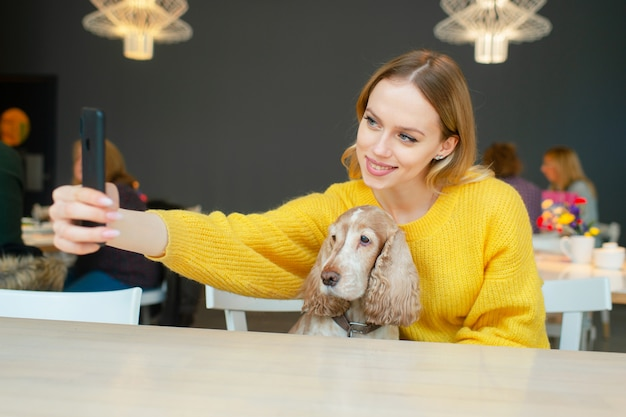 Жизнерадостная молодая белокурая женщина держа собаку кокер-спаниеля на ее коленях и принимая selfie с smartphone