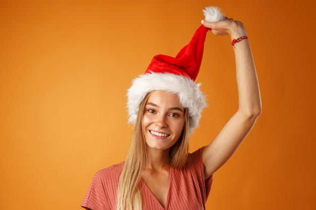 오렌지 배경 산타 모자를 쓰고 쾌활 한 젊은 금발의 여자.