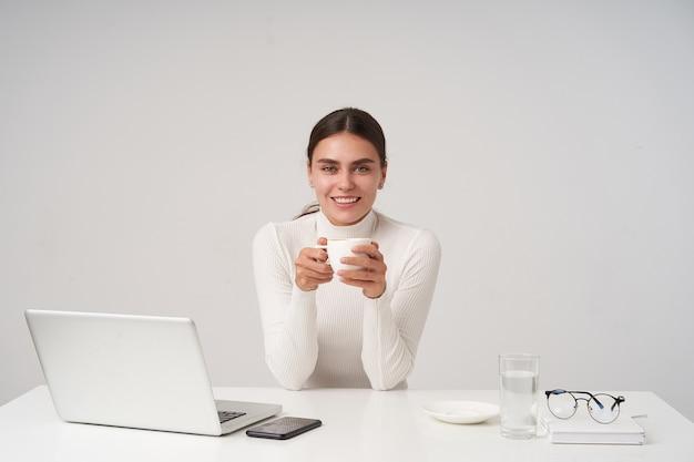 上げられた手でお茶を保持し、白い壁の上にポーズをとって、カメラで幸せそうに笑って、自然なメイクで陽気な若い青い目の暗い髪の女性