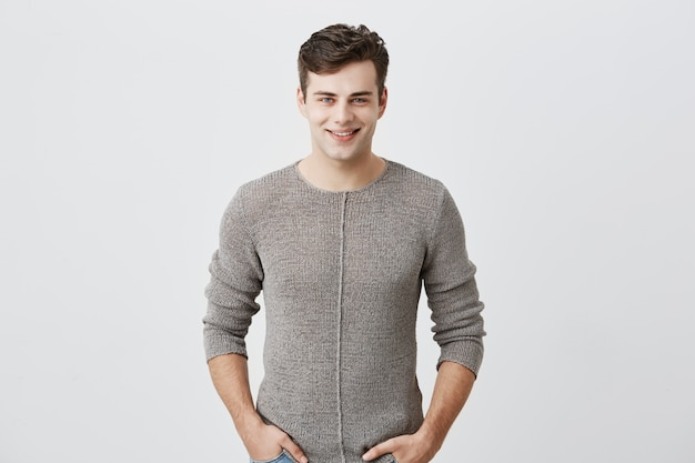 Cheerful young blue-eyed man with dark hair posing in studio with happy smile, handsome fit man dressed casually smiling joyfully, showing his white straight teeth. positive emotions concept.
