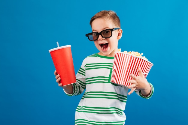 Cheerful young boy in eyeglasses preparing to watch the film