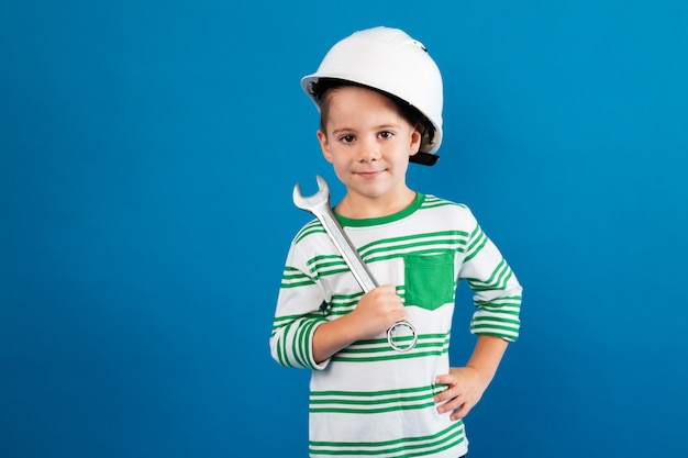 Cheerful young boy in protective helmet posing with wrench
