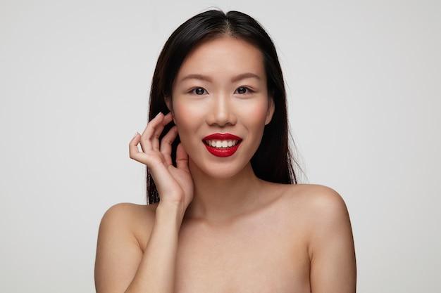 Allegro giovane donna bruna dagli occhi marroni guardando positivamente e sorridente ampiamente, toccando delicatamente il viso con la mano alzata mentre posa sopra il muro bianco