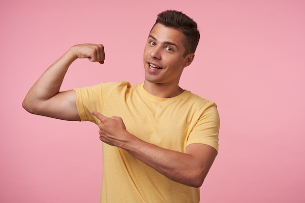 Cheerful young brown-eyed brunette male with short haircut smiling happily at camera while pointing with forefinger on his strong biceps, isolated over pink background