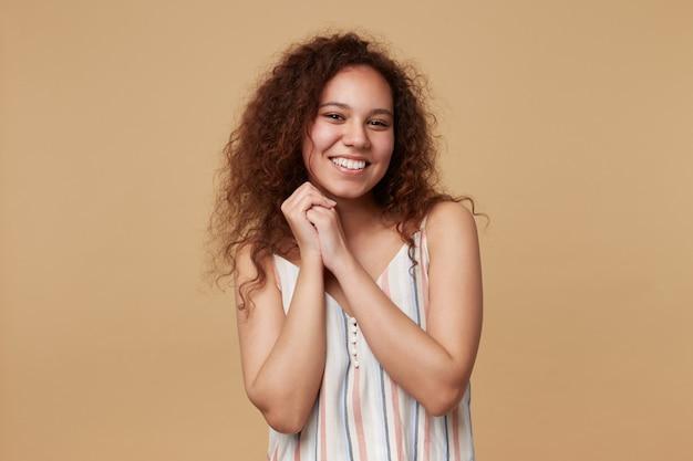 베이지 색에 고립 된 매력적인 미소로 그녀의 얼굴에서 접힌 손을 유지하는 캐주얼 헤어 스타일로 쾌활한 젊은 갈색 눈동자 곱슬 갈색 머리 여자