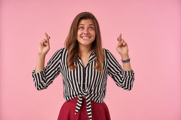 Веселая молодая брюнетка женщина счастливо смотрит вверх и скрещивает пальцы, загадывая желание, в полосатой рубашке и красной юбке, стоя на розовом