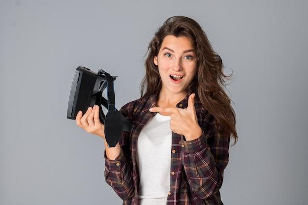 회색 배경 스튜디오에서 가상 현실 안경을 테스트하는 쾌활한 젊은 갈색 머리 소녀