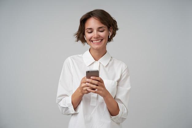 Веселая молодая брюнетка с короткой стрижкой держит мобильный телефон в поднятых руках и счастливо смотрит на экран, одетая в формальную одежду, стоя