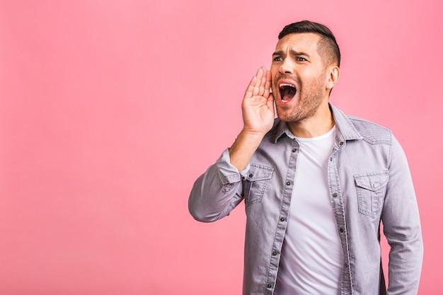Веселый молодой брюнетка человек в случайном холдинге за руку рядом с открытым ртом