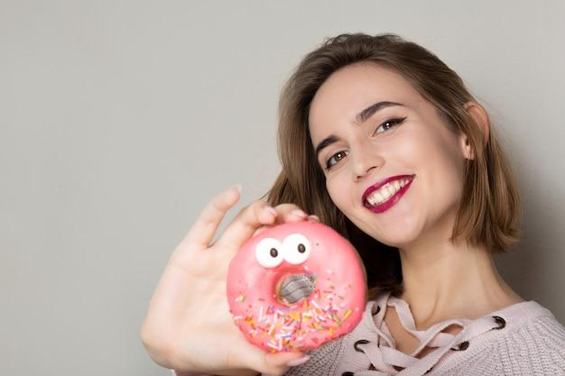 灰色の背景の近くでポーズをとってピンクの釉薬と甘いドーナツを保持している陽気な若いブルネットの女性