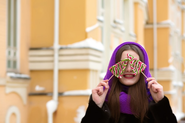 Cheerful young  brunette woman in purple scarf having fun with the colorful christmas candies