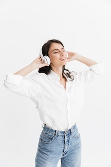 白い壁の上に孤立して立っているシャツを着て、ヘッドフォンで音楽を聴いて陽気な若いブルネットの女性