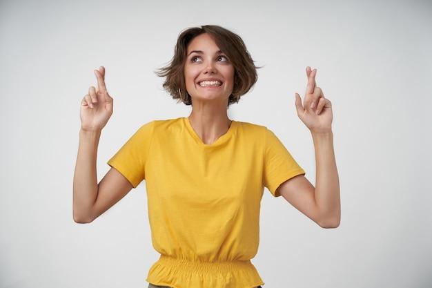Allegra giovane donna bruna con taglio di capelli corto alzando le mani con gli indici incrociati, essendo positivo e volendo che i suoi desideri si avverino, in posa in maglietta gialla