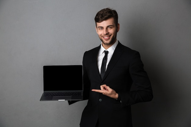 Cheerful young business man showing display of laptop computer