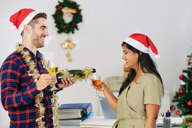 Веселые молодые деловые люди пьют шампанское во время празднования рождества в офисе