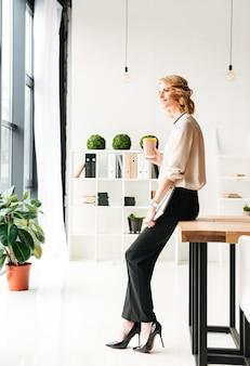 コーヒーを飲みながらよそ見ラップトップコンピューターを保持している陽気な若いビジネス女性。