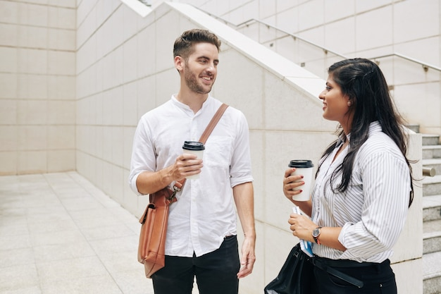 Cheerful young businessman and businesswoman drinking take out coffee when standing outside office building
