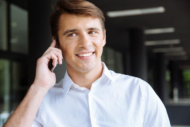 쾌활 한 젊은 사업가 노트북을 들고와 비즈니스 센터 근처 휴대 전화에 대 한 얘기