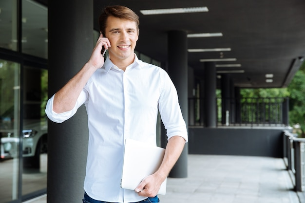 Cheerful young businessman holding laptop and talking on mobile phone near business center