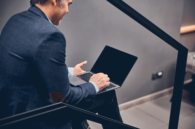 Cheerful young businessman holding laptop with black screen while sitting at the office