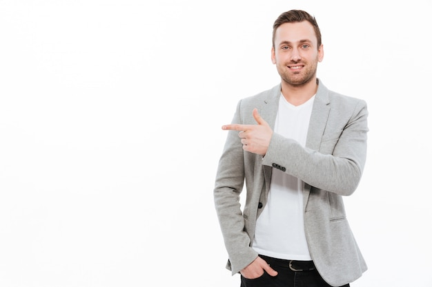 Cheerful young businessman pointing.
