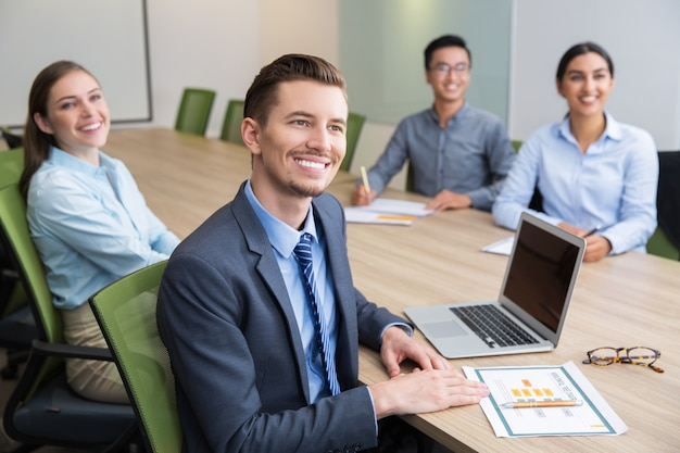 Cheerful young businessman sitting at seminar
