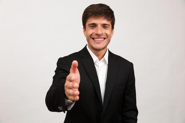白い壁に孤立して立っている陽気な青年実業家は握手のためにあなたに手を差し伸べます。