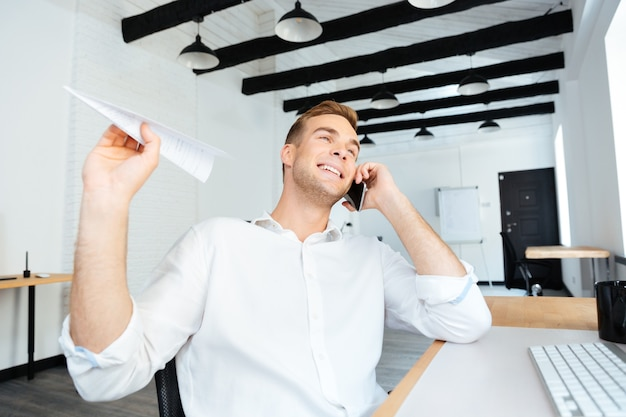 Cheerful young businessman talking on cell phone and throwing paper plane in office
