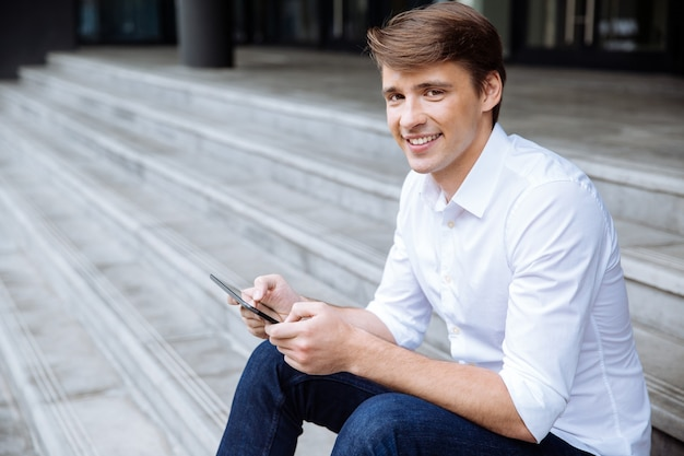 Cheerful young businessman using smartphone near business center