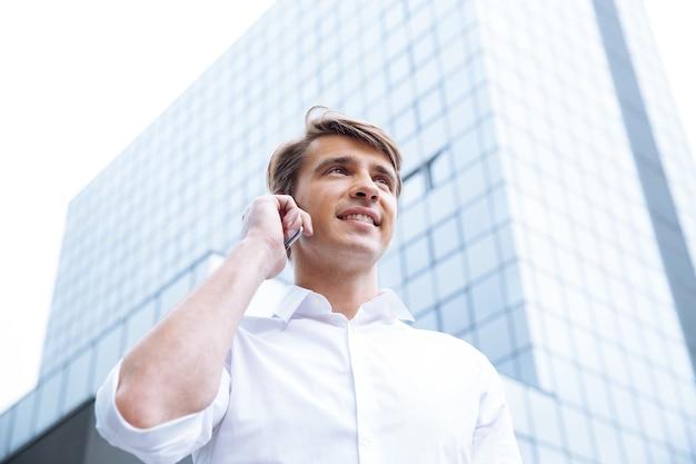 ビジネスセンターの近くでスマートフォンを使用して陽気な青年実業家